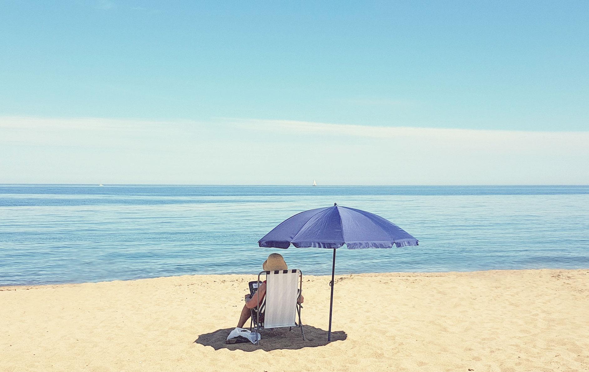 En person som sitter i en solstol på Tobisviks Campings strand.
